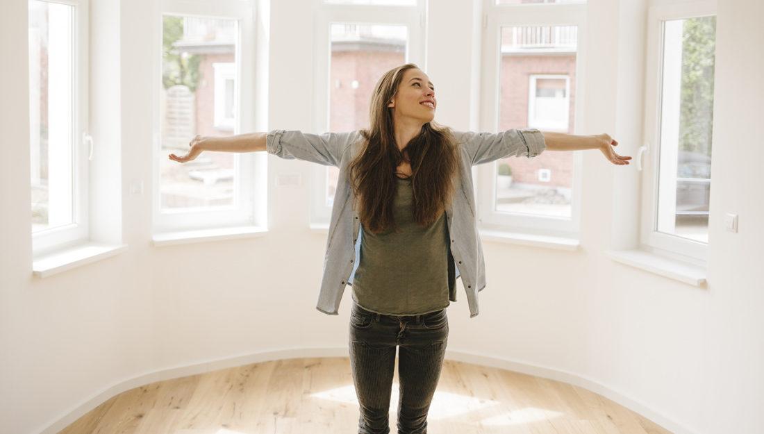 Bilde av en ung kvinne i sin nye, og foreløpig tomme, leilighet